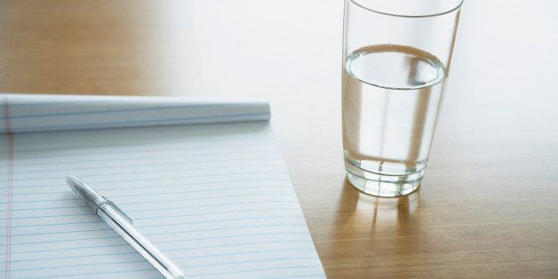 Notepad with a pen lying on it and glass of water on a table