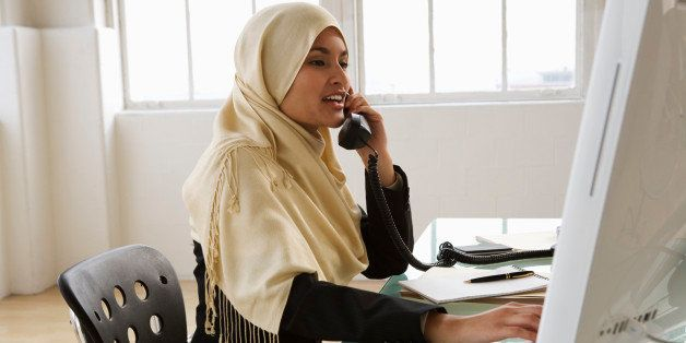 Young businesswoman using telephone at desk