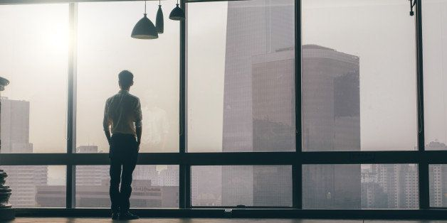 Businessman looking at cityscape from office