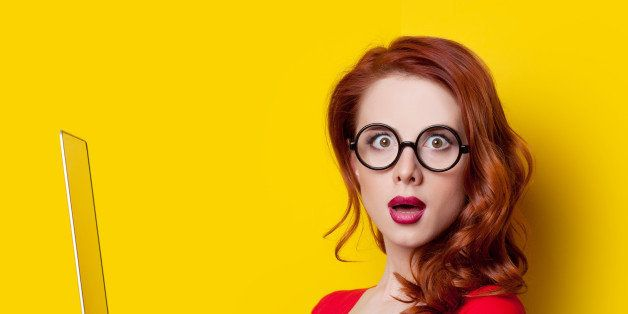Surprised redhead girl with laptop computer in red dress on yellow background.