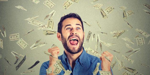 Portrait happy man exults pumping fists ecstatic celebrates success screaming under money rain falling down dollar bills bank