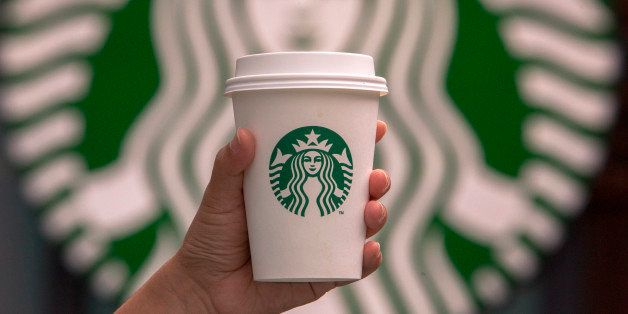 CHENGDU, SICHUAN PROVINCE, CHINA - 2015/09/13: Hand holding a cup of coffee in front of Starbucks logo. Starbucks is streamli