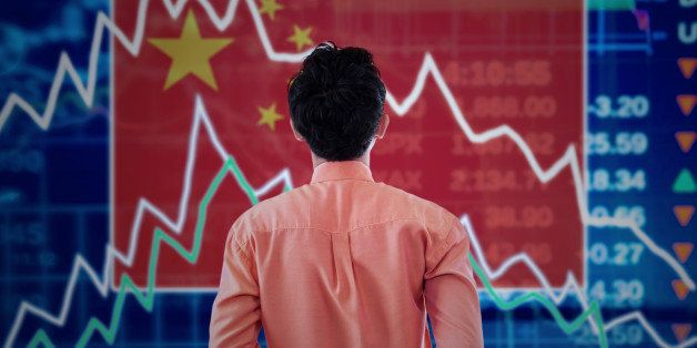 Young male broker looking at a stock market of china with declining arrows