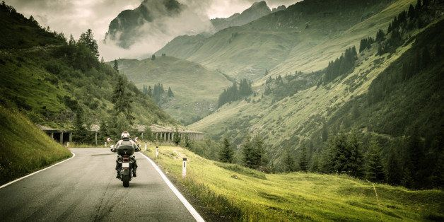 Motorcyclist on mountainous highway, cold overcast weather, Europe, Austria, Alps, extreme sport, active lifestyle, adventure
