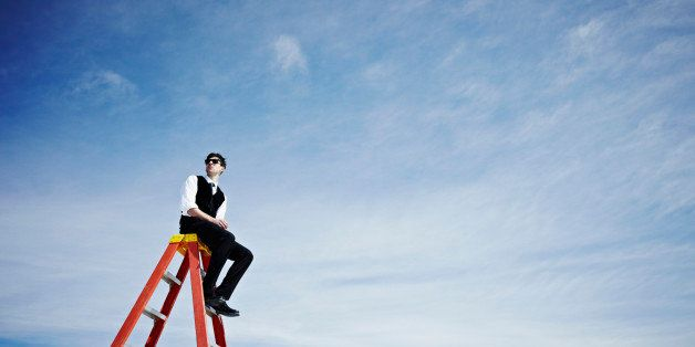 Businessman sitting on top of ladder wearing sunglasses looking out
