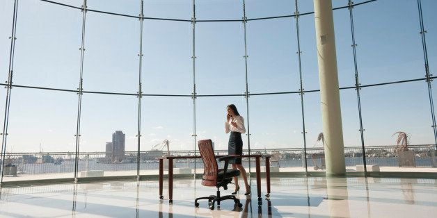 Businesswoman working in large office with glass wall