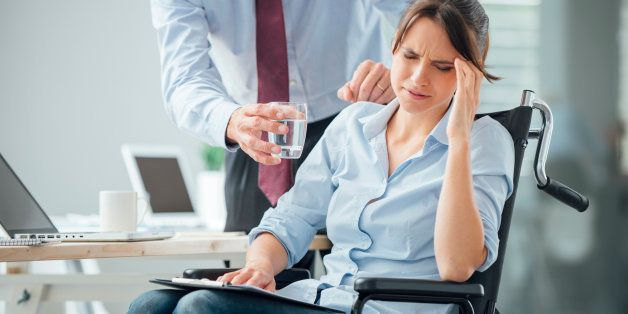 Business woman in wheelchair having an headache at office, her collegue is giving her a glass of water and helping her