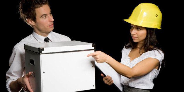 Business woman with hard helmet delegating a businessman