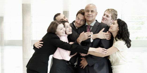 Group of business people hugging one person