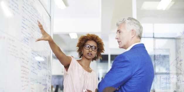 Young businesswoman explaining strategy on whiteboard to male colleague in creative workspace