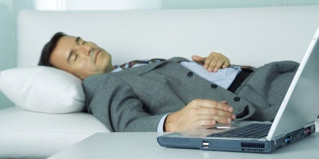 Businessman sleeping on sofa, hand resting on laptop