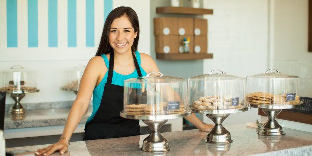 Cute young Hispanic woman standing across the counter in her cake shop and smiling