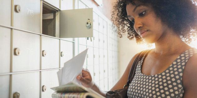Mixed race businesswoman checking mailbox