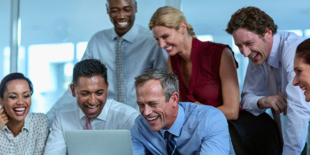 Happy multi-ethnic businesspeople having video conference in office