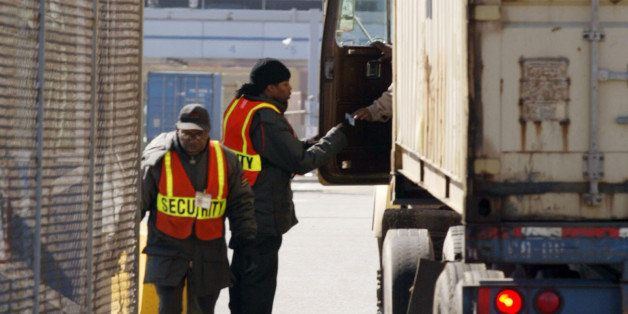 Security personnel check with the driver of a tractor trailer at the main gate entrance to the Seagirt Terminal in Baltimore,