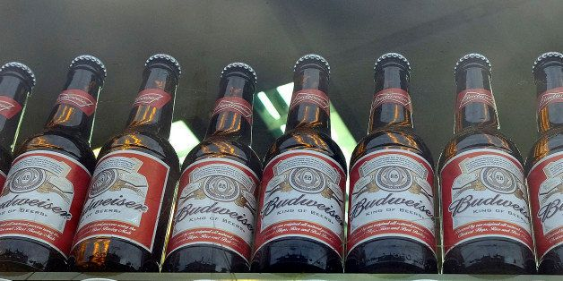 FILE - This is a Tuesday, Oct. 13, 2015 file photo of bottles of Budweiser beer in a shop window in London. Budweiser maker A