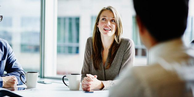 Businesswoman leading project discussion during morning meeting in office
