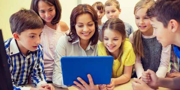 education, elementary school, learning, technology and people concept - group of school kids with teacher looking to tablet p