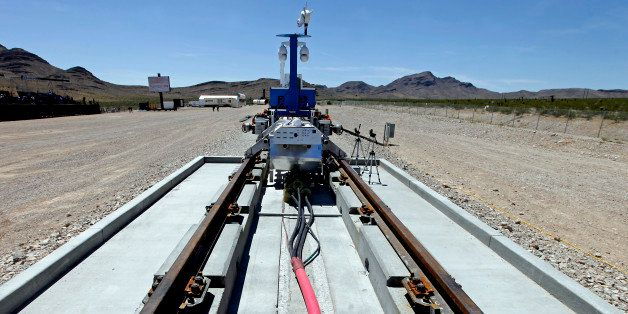 A recovery vehicle and a test sled sit on rails after the first test of the propulsion system at the Hyperloop One Test and S