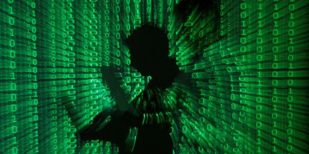 An illustration picture shows a projection of binary code on a man holding a laptop computer, in an office in Warsaw June 24,