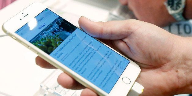 FILE - In this Sept. 19, 2014, file photo, a customer looks at the screen size on an iPhone 6 Plus while waiting in line to u