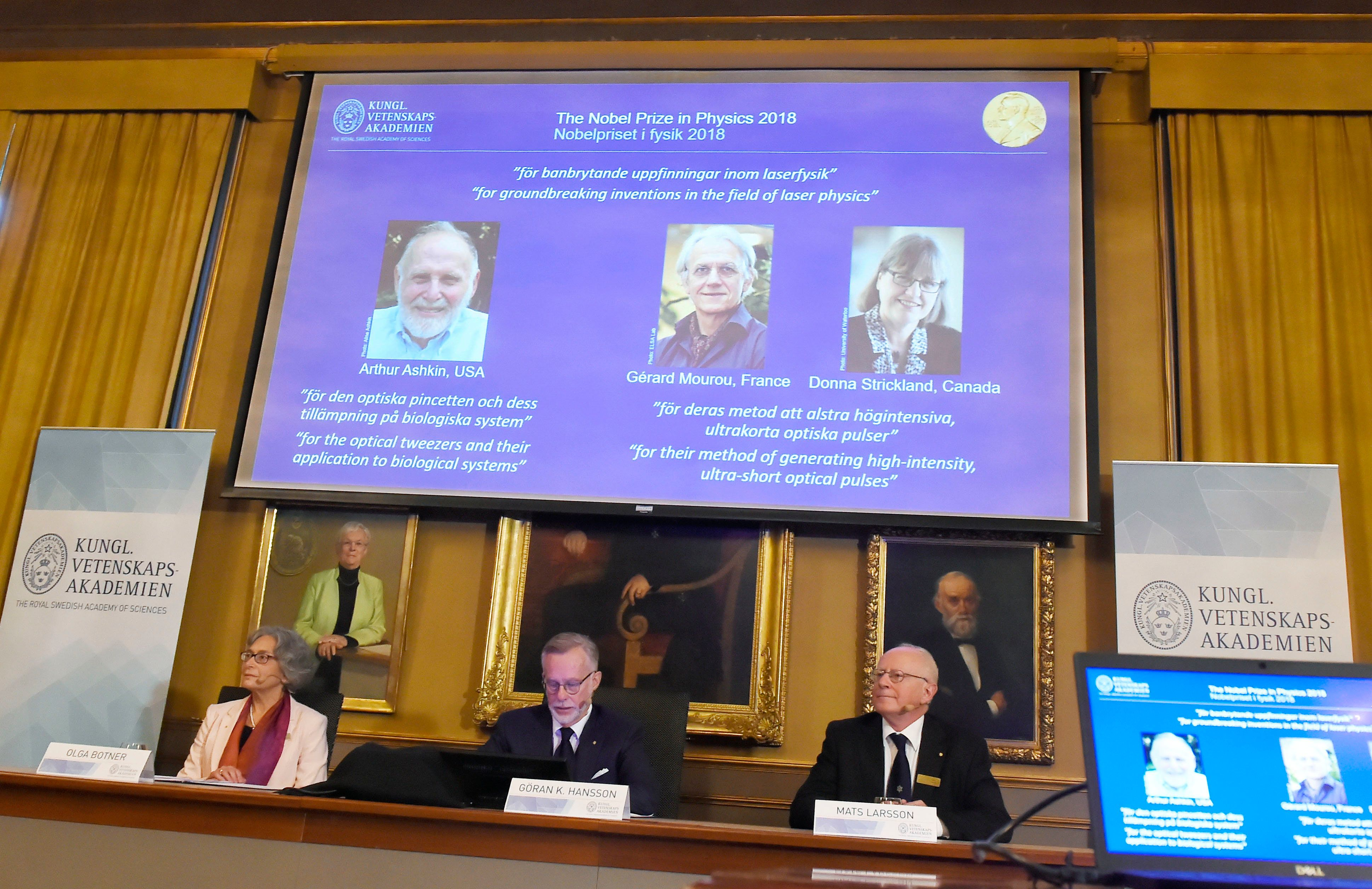 Members of the Nobel Committee for Physics (L-R) Olga Botner, Goran K Hansson and Mats Larsson sit in front of a screen displaying portraits of Arthur Ashkin of the United States, Gerard Mourou of France and Donna Strickland of Canada during the announcement of the winners of the 2018 Nobel Prize in Physics at the Royal Swedish Academy of Sciences on October 2, 2018 in Stockholm. - The Nobel Prize laureates for physics 2018 Arthur Ashkin of the United States won one half of the prize, while Gerard Mourou of France and Donna Strickland of Canada shared the other half. (Photo by Hanna FRANZEN / TT News Agency / AFP) / Sweden OUT        (Photo credit should read HANNA FRANZEN/AFP/Getty Images)