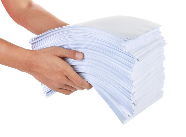 a stack of paper in his hand...