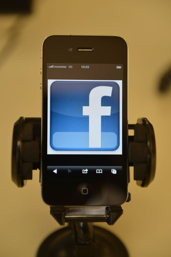 A mobile phone showing a Facebook page, in Quito, on May 10, 2012.  AFP PHOTO/RODRIGO BUENDIA        (Photo credit should rea
