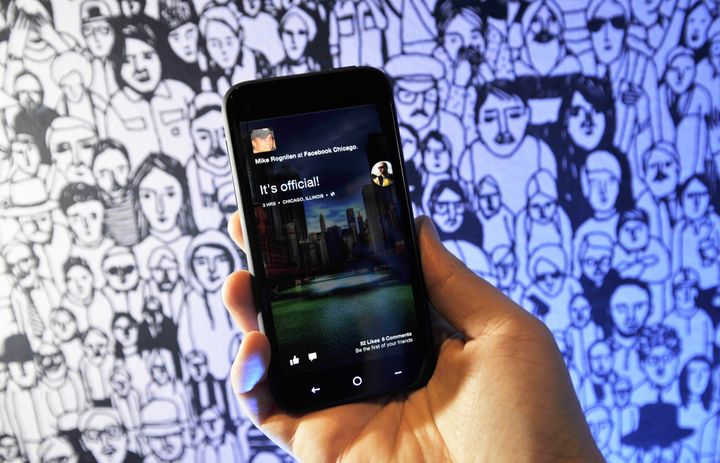 A Facebook employee displays an HTC phone with the new Home operating system against the backdrop of a decorated wall at Face