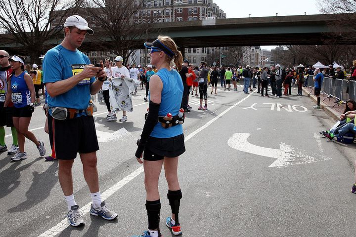 BOSTON, MA - APRIL 15:  A runner uses his phone as others gather near Kenmore Square after two bombs exploded during the 117t