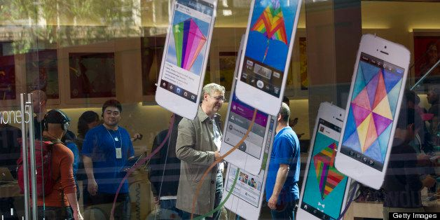 Customers talk with employees inside an Apple Inc. store in San Francisco, California, U.S., on Friday, April 19, 2013. Apple