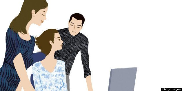 Two people helping a woman at a computer