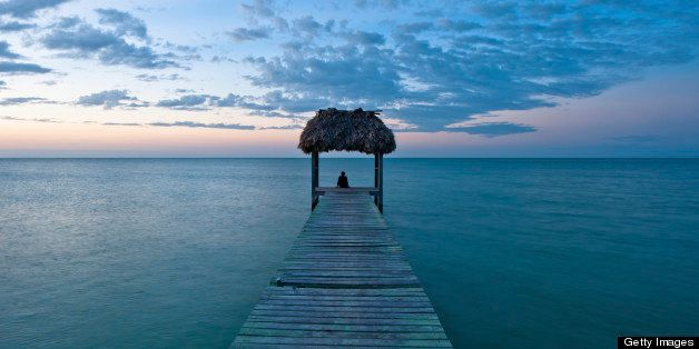 This is an image of a beautiful sunset in the Carribean taken from a dock on the beach with a palm thatched roof.