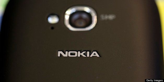 A camera lens and a logo are seen on the reverse side of a Nokia Oyj Lumia 710 smartphone displayed inside a Carphone Warehou