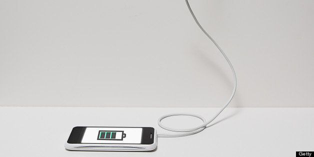 Smart phone plugged into electrical outlet, white phone, wall and floor