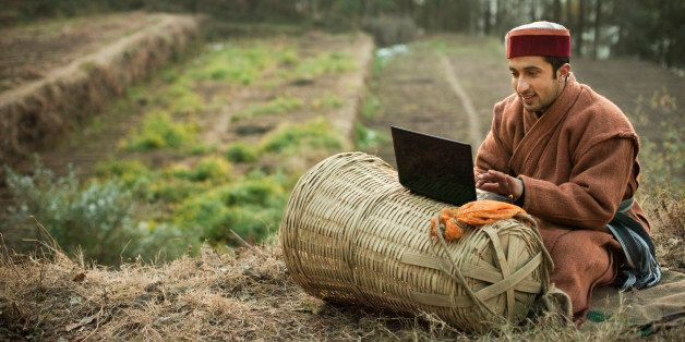 People of Himachal Pradesh: Young farmer using laptop, he is sitting in terraced field wearing traditional winter dress of Hi