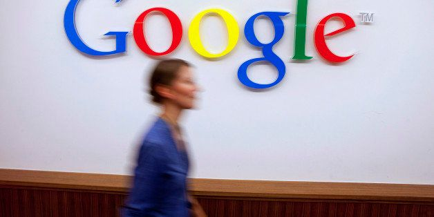 A Google Inc. employee walks past a logo outside the entrance to the company's offices in Berlin, Germany, on Friday, Aug. 16