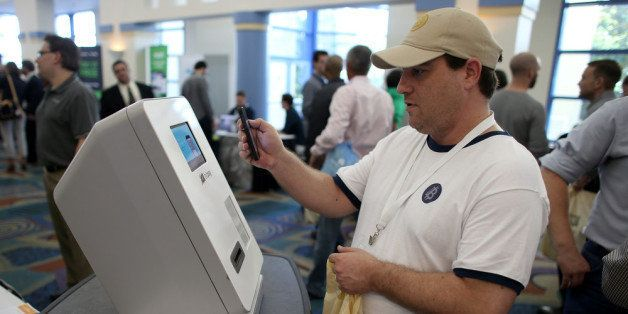 MIAMI BEACH, FL - JANUARY 25:  Eric Cogen uses a Bitcoin ATM to add bitcoins to his account while attending the North America