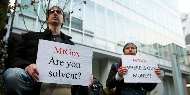 Kolin Burges, right, and another Mt. Gox customer hold placards while protesting outside a building housing the headquarters