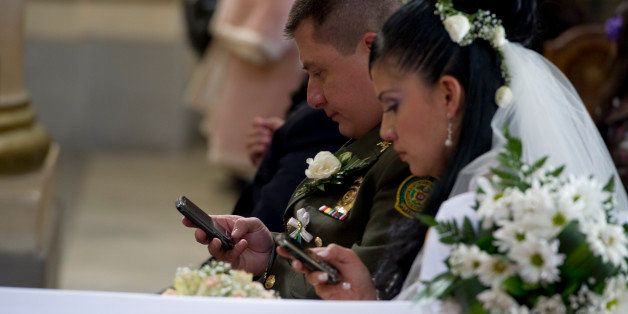 A bride and groom use their mobile phones during a mass wedding of police officers at the Cathedral of Bogota, on December 9,