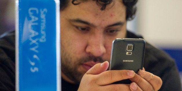 A customer looks at the new Samsung Electronics Co. Galaxy S5 smartphone on display at a Best Buy Co. store in San Francisco, California, U.S., on Friday, April 11, 2014. The S5 features a 5.1-inch screen with a fingerprint reader, 16-megapixel camera, heart-rate sensor, water-resistant coating that can withstand 30 minutes at the bottom of a meter-deep (3-foot deep) pond, and a back resembling dimpled leather. Photographer: David Paul Morris/Bloomberg via Getty Images