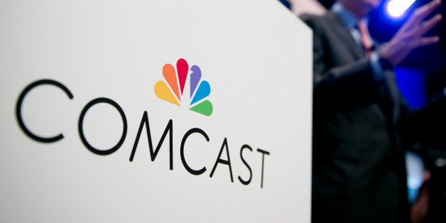 The Comcast Corp. logo is seen as Brian Roberts, chairman and chief executive officer of Comcast Corp., right, speaks during