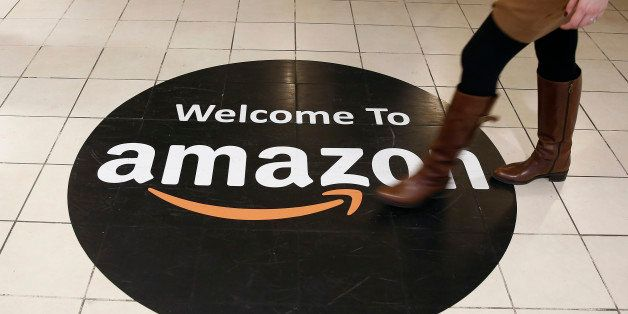 An employee walks over a logo on the floor of Amazon.com Inc.'s fulfillment centers in Rugeley, U.K., on Monday, Dec. 2, 2013