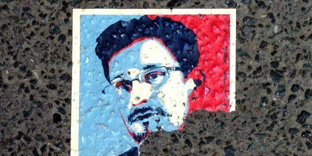 A sticker featuring fugitive US intelligence leaker Edward Snowden and partially reading 'asylum' is seen on the pavement in