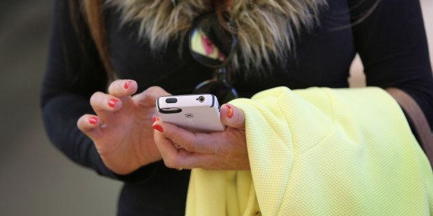 NEW YORK, NY - APRIL 22:  A woman uses an Iphone at Apple's Fifth Avenue store on Earth Day in Midtown Manhattan on April 22,