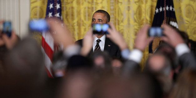 WASHINGTON, DC - JANUARY 23:  Obsucred by guests' mobile phone cameras, U.S. President Barack Obama delivers remarks before t