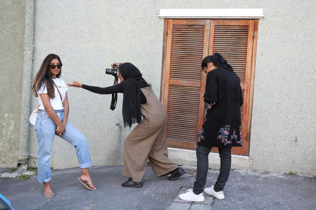 Young women taking photographs outside the Auwal Mosque in