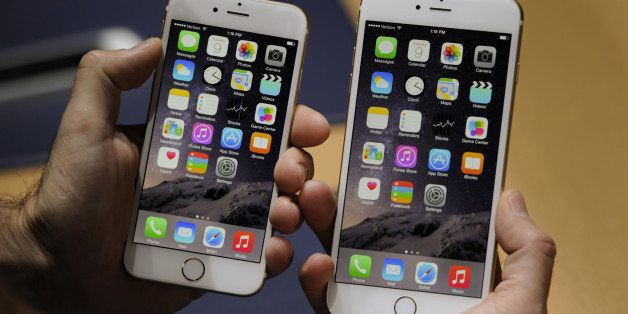An attendee displays the new Apple Inc. iPhone 6, left, and iPhone 6 Plus for a photograph after a product announcement at Fl