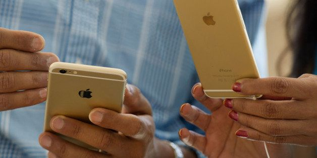 Customers compare an Apple Inc. iPhone 6, left, and iPhone 6 plus during the sales launch at an Apple store in Palo Alto, Cal