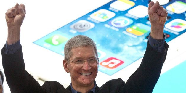 FILE - In this Jan. 17, 2014 file photo, Apple's CEO Tim Cook, left, gestures as China Mobile Chairman Xi Guohua smiles durin